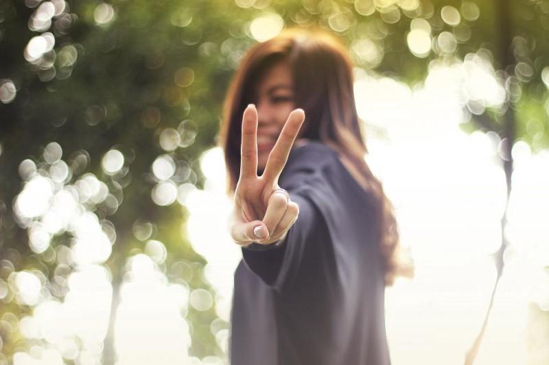 An Asian girl extends the peace sign towards the camera