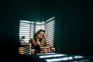 A girls its in the corner of her room and the light from the window casts shadows on her face.