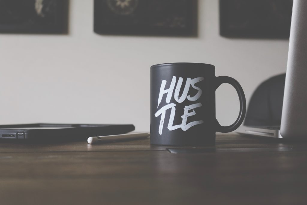 "A coffee mug on a desk with a laptop; the coffee mug says ""HUSTLE"" on it"