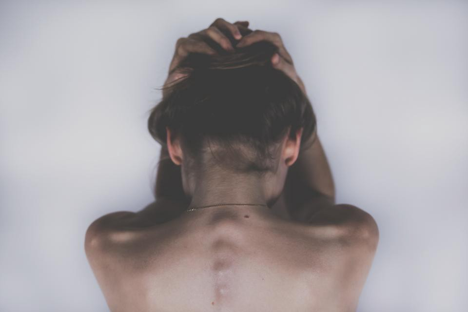 A woman crouches over, bare-back and holder her head in her hands