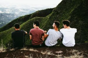 Friends laughing looking over a cliff