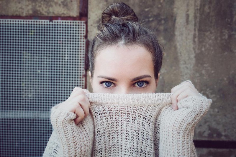 Girl holding her sweater up to her nose