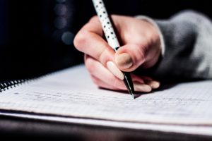 A hand on an exam paper with a pencil