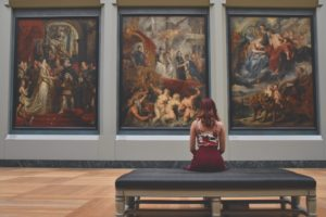 A young woman sits on a bench in an art gallery, looking at panels of paintings