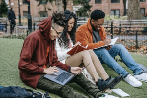 this picture has three university students with books and laptops sitting on the grass.